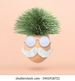 Fluffy creative Easter egg made of green grass, sunglasses and mustache on pastel pink background. Minimal spring concept. Flat lay.