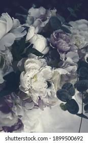 Fluffy dark purple peonies flowers. Creative bouquet in vintage.