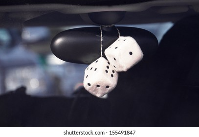 Fluffy dice hanging off the rear view mirror of a car, boy racer style.