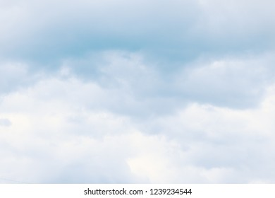 Fluffy dreamy clouds in light blue sky. For background and wallpaper
