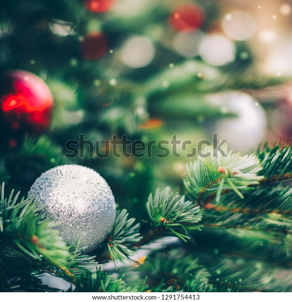 Fluffy fir decorated with silver glitter bauble close up. Christmas and new year background
