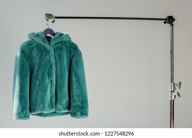 fluffy green faux fur coat hanging on rack at grey background with sunbeams