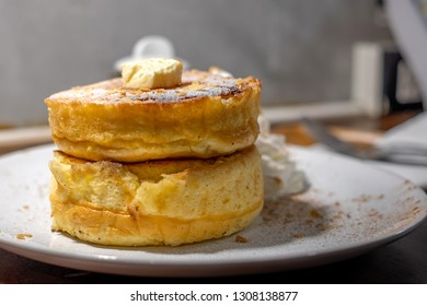 Fluffy Japan souffle pancakes, hotcakes with honey syrup and butter light concrete closeup