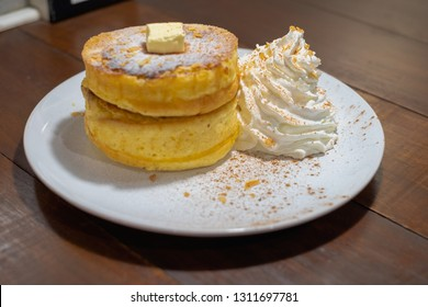 Fluffy Japan souffle pancakes, hotcakes with honey syrup and butter light concrete background copy space