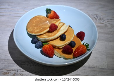 Fluffy japanese pancakes with berries isolated on white wooden table.