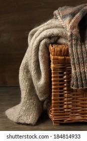 Fluffy knitted sweaters on wicker basket.