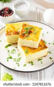 Fluffy omelet baked with zucchini, kids healthy Breakfast, delicious casserole. On white wooden background, stack on plate