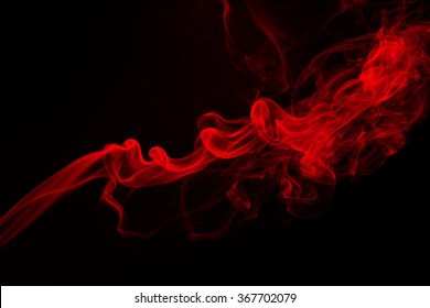 Fluffy puffs of red smoke and fog on black background, fire design and darkness concept