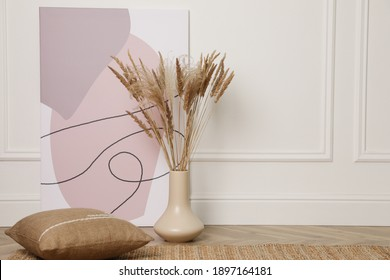 Fluffy reed plumes and painting near white wall indoors, space for text. Interior elements