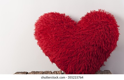 Fluffy soft red heart. Pillow on wood bord.