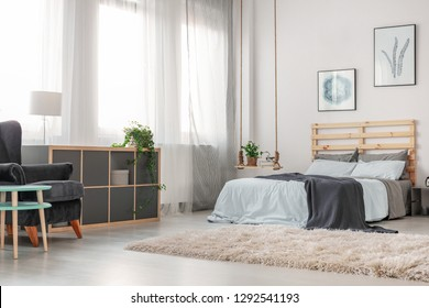 Fluffy white carpet on the floor of trendy bedroom with king size bed with wooden headboard, posters on the wall and fashionable swing as nightstand