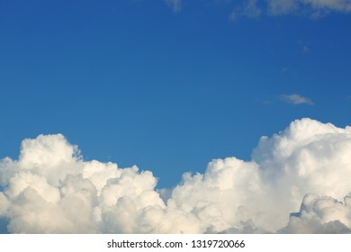 fluffy white cloud above clear blue sky background