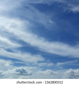fluffy white cloud moving above clear blue sky