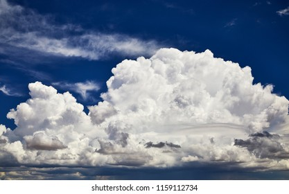 Fluffy white clouds against a blue sky