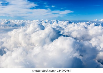 Fluffy white clouds and blue sky seen from airplane.