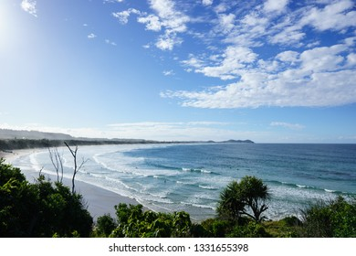 Fluffy white clouds gather over gentle surf in a beautiful wide bay, east coast of Australia.
