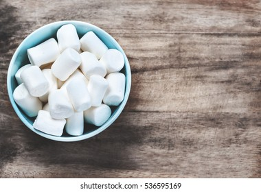 Fluffy white marshmallow in blue round  bowl on old wooden table with copy space close up.
