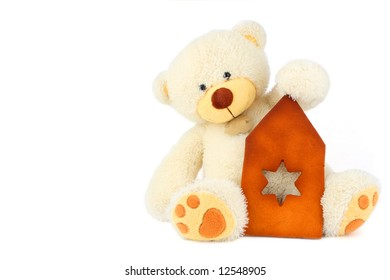 fluffy white teddy bear and part of gingerbread house