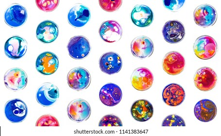 Fluid art in a petri dish. Colorful acrylic, ink, oil and watercolor marble paint splashes. Abstract fluid ocean of color or alien planet of liquid color.  Living colorful bacteria in a petri dish.