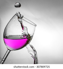 Fluid motion of coloured water in a wine glass.