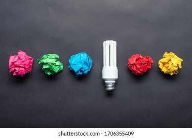 Fluorescent lamp and crumpled colorful paper balls on black background. Successful solution of problem. Idea generation and brainstorming motivation. Great idea among failing ideas metaphor.