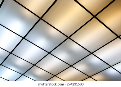 Fluorescent lamps on the modern ceiling. Luminous ceiling of square tiles.