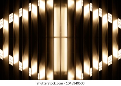 Fluorescent lights visible through grid or louvers. Abstract image on the subject of contemporary architecture, industry or technology.