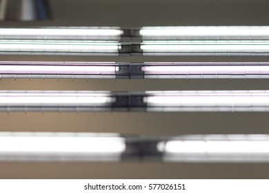Fluorescent office lights. Industrial style hanging office lights. Close view angled from above.