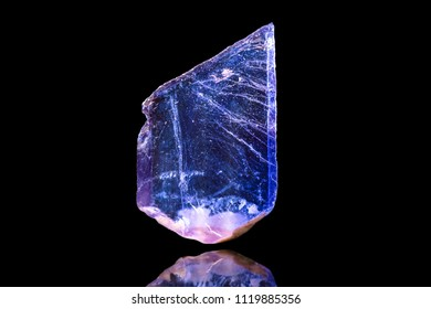 Fluorite or fluorspar mineral in front of black background, raw crystal specimen
