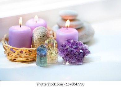 fluorite, quartz, amethyst geode crystal, candles on white background. Spa therapy composition with healing gemstones. Crystal Ritual, Esoteric, meditation, relax, life balance concept.