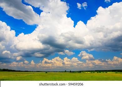 Flurry cumulus clouds and green meadow below.