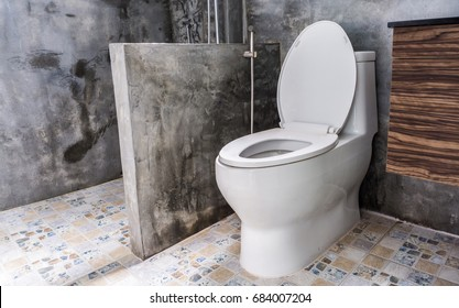 Flush toilet in Modern loft Bathroom with cement wall background