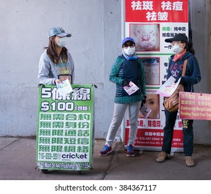 Flushing, New York - June 03 2015: Three girls wearing masks advertising different services in the street.