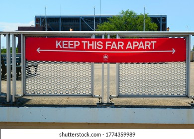 Flushing, Queens,NY,USA. July 6.2020:Social distancing sign with an indication of 6 feet distance. The sign on the fence of corona park. Back ground is USTA Billie Jean King National Tennis Center.
