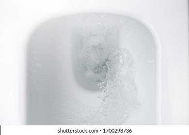 Flushing the water in the white toilet. Close up.
