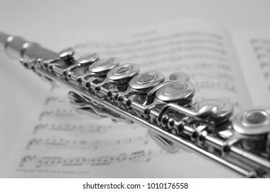 Flute closeup with sheet music in monochrome
