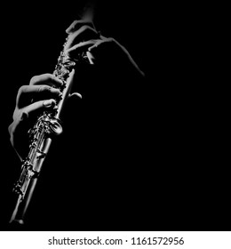 Flute instrument. Flutist hands playing flute music. Player with orchestra instrument closeup. Flute isolated on black