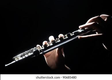 Flute music instrument details playing. Hand of flutist musician on black