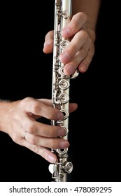 Flute in the musician's hands on a black background