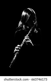 Flute player. Flutist playing flute instrument. Classical musician isolated on black