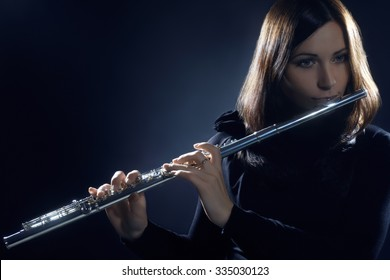 Flute player flutist playing music instrument. Classical musician woman playing flute