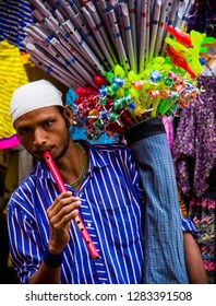 A flute seller.  A flute selleer carrying his flutes and some other toys to sell on the streets of Pushkar. Captured on 22 November 2018 in Pushkar, Rajasthan.