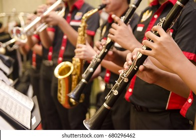 flute, trumpet and saxophones orchestra perform by high school boy