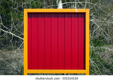 A fluted bright red metal plate in a bright yellow metal frame on the background of a forest. Russia, city of Novosibirsk, May 2015.