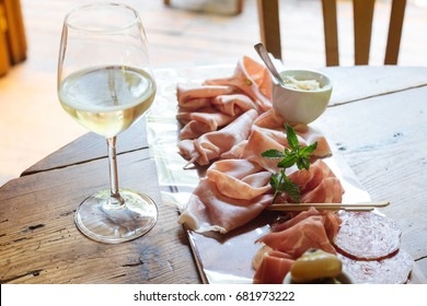 Flutes filled with sparkling prosecco, in a restaurant in Conegliano, and starter dish on a cutting board with salami, Trieste's ham, raw ham of Parma and mortadella, with horseradish as a sauce