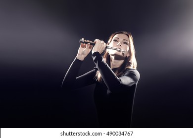 Flutist playing Flute piccolo instrument. Flute player woman musician with music instrument