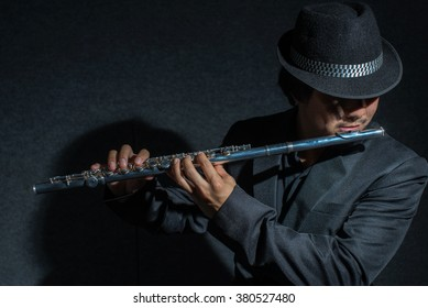 flutist playing music in dark,low key image