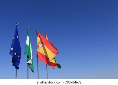Fluttering flags of European Union, Andalusia, Spain and Granada on top of Watch Tower (Torre de la Vela) of Alcazaba fortress at the historical Alhambra Palace complex in Granada, Andalusia, Spain.
