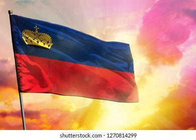 Fluttering Liechtenstein flag on beautiful colorful sunset or sunrise background. Liechtenstein success and happiness concept.