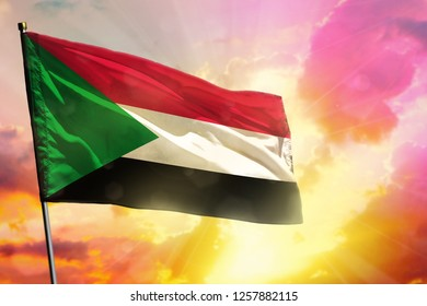 Fluttering Sudan flag on beautiful colorful sunset or sunrise background. Sudan success and happiness concept.